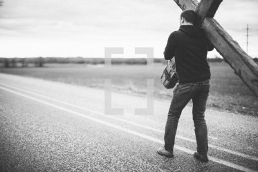 lightstock-61191-man-carrying-a-large-cross-along-the-center-lines-of-a-highway-re--2